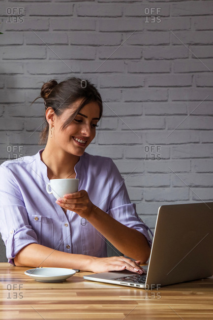 Smiling young female remote employee with cup of coffee in hand sitting at table and browsing laptop while working online from home