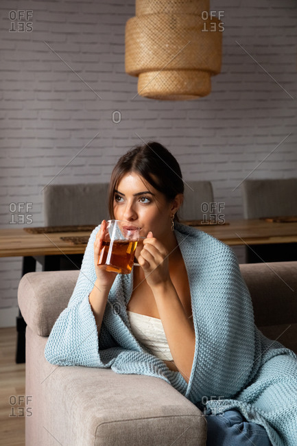 Pensive young female wrapped in warm blanket sitting on couch and enjoying hot tea while chilling in cozy living room at home