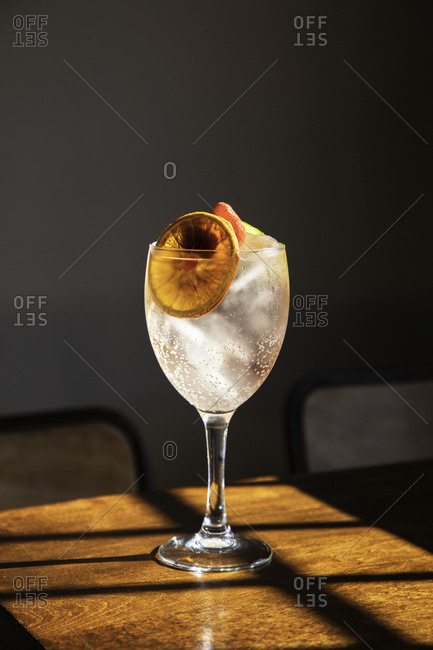Crystal goblet with cold alcohol cocktail with ice and sliced orange placed on wooden table in bar