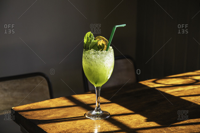 Glass of fresh appetizing icy cocktail with mint and lemon slice served with straw on wooden table in pub