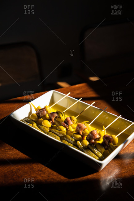 High angle of tray with delicious skewers with fish and olives served with marinated pickled cucumbers on wooden table
