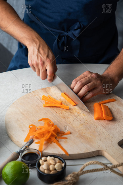 Crop unrecognizable cook chopping fresh carrot on wooden cutting board in kitchen