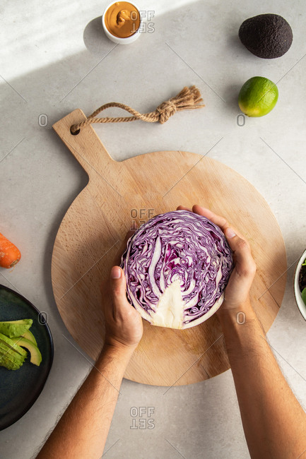 Top view of crop anonymous person placing halved fresh red cabbage on wooden cutting board while preparing delicious salad in kitchen