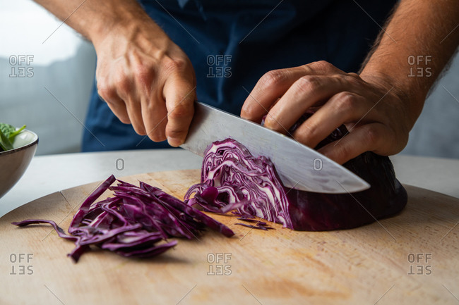 Crop anonymous cook chopping fresh natural red cabbage on wooden cutting board while preparing healthy dish in kitchen