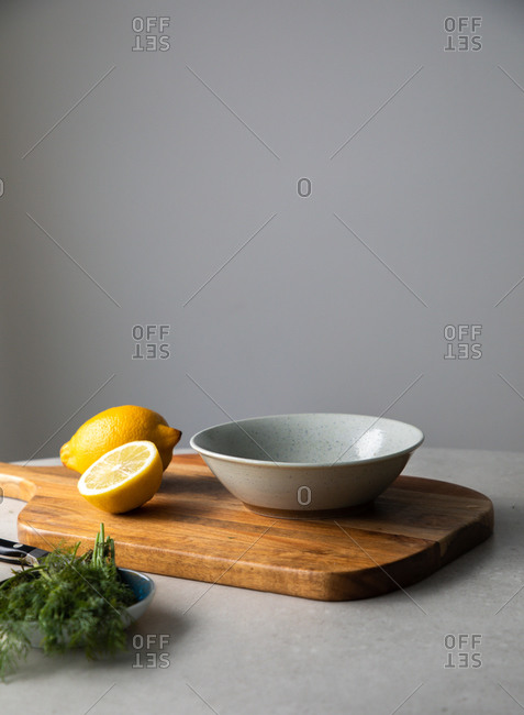 Fresh cut lemon and bunch of green dill placed with bowl and wooden cutting board on kitchen table during cooking