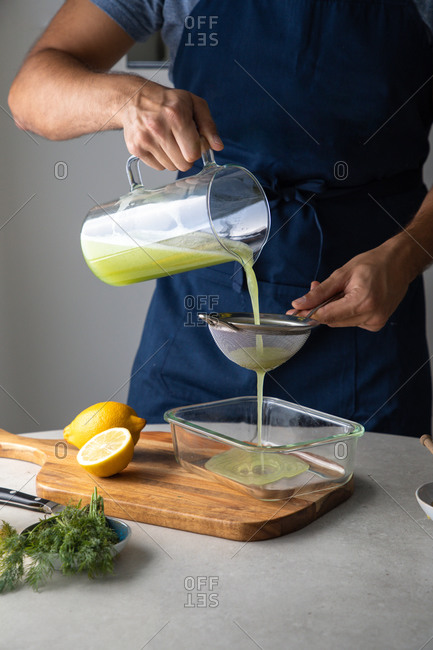 Crop anonymous male cook filtering fresh green drink from blender cup through sieve while preparing healthy breakfast in kitchen