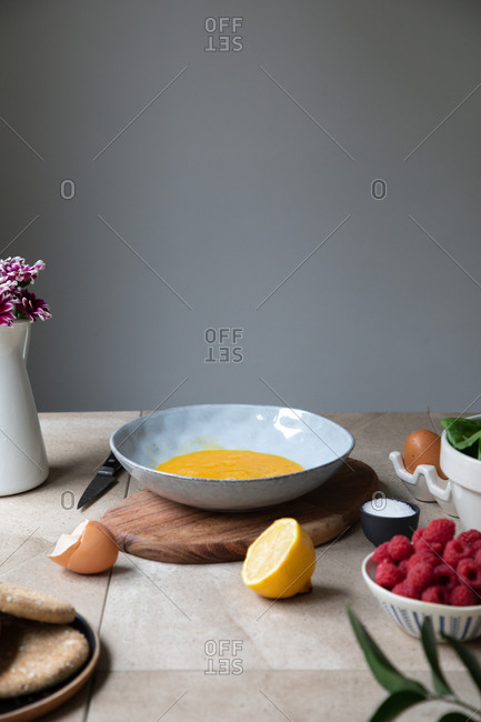 Bowl with mixed eggs placed near fresh berries and lemon on kitchen table with ingredients for recipe