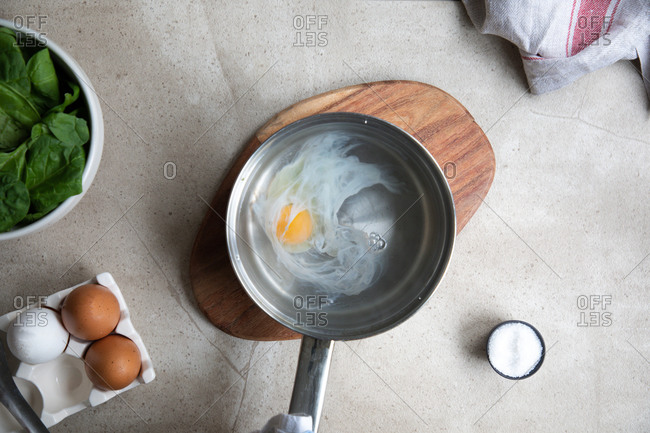 Top view of metal saucepan with boiling water and egg during poached eggs preparation on kitchen table with ingredients
