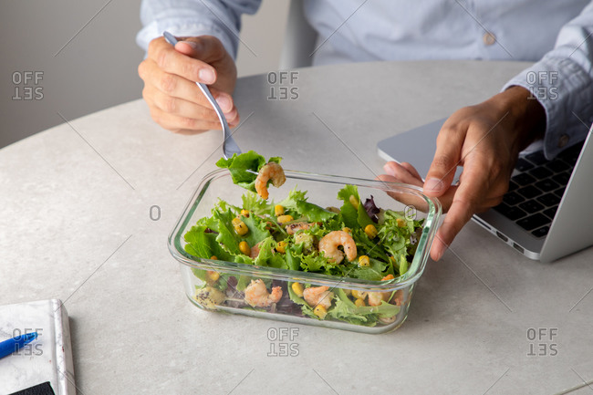 Crop view of unrecognizable office employee sitting at table in workplace and eating delicious salad with greenery and shrimps while having nutritious lunch