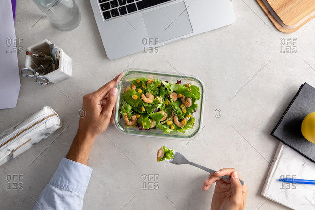 From above of unrecognizable office employee sitting at table in workplace and eating delicious salad with greenery and shrimps while having nutritious lunch