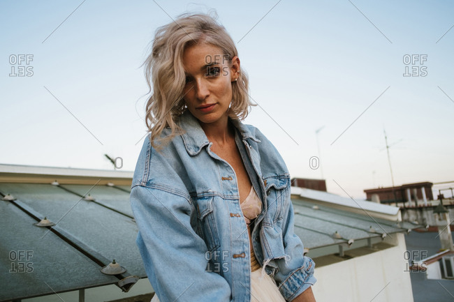 Tranquil female in denim jacket and with wavy hair relaxing in house roof in the city in evening and looking at camera