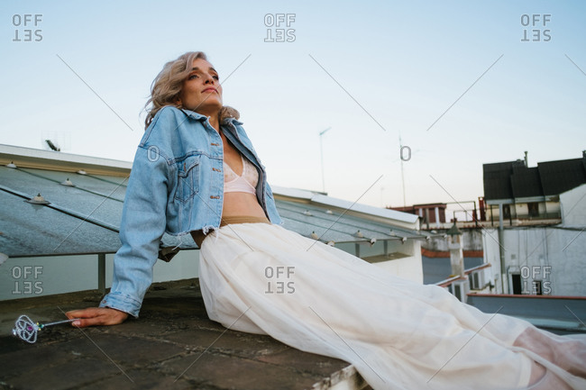Tranquil female in denim jacket and with wavy hair relaxing in house roof in the city in evening and looking away