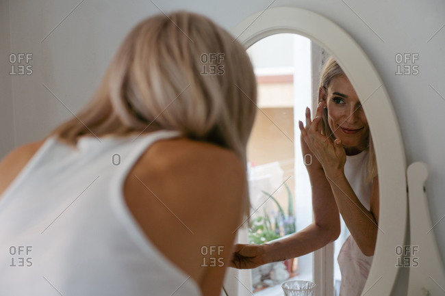 Charming female applying lip pencil and doing makeup at home while reflecting in mirror