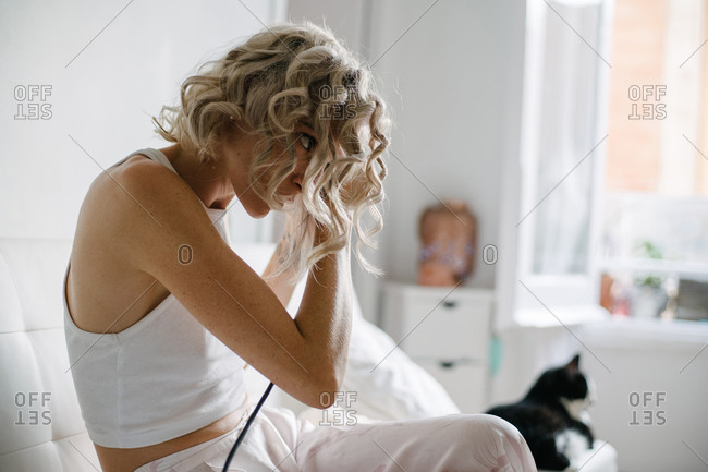Side view of female in domestic wear sitting on sofa at home and curling hair with iron