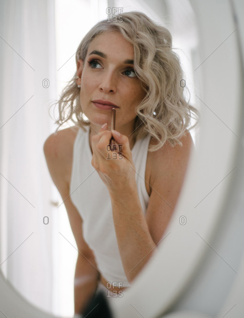 Low angle of charming female applying lip pencil and doing makeup at home while reflecting in mirror