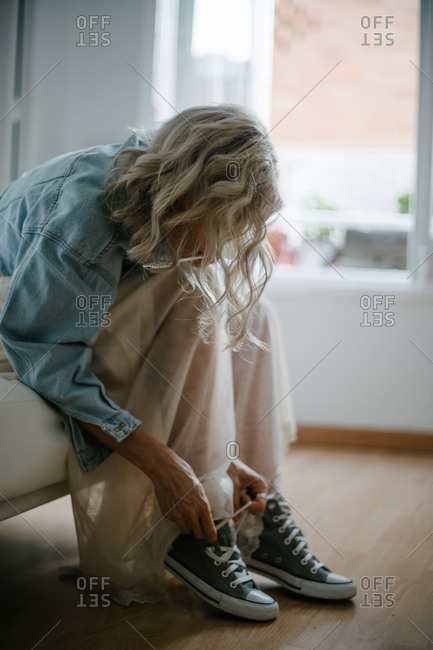 Side view of stylish female in denim jacket and skirt sitting on sofa and tying shoelaces on gumshoes