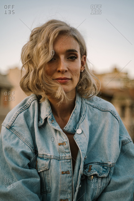 Tranquil female in denim jacket and with wavy hair relaxing in city in evening and looking at camera