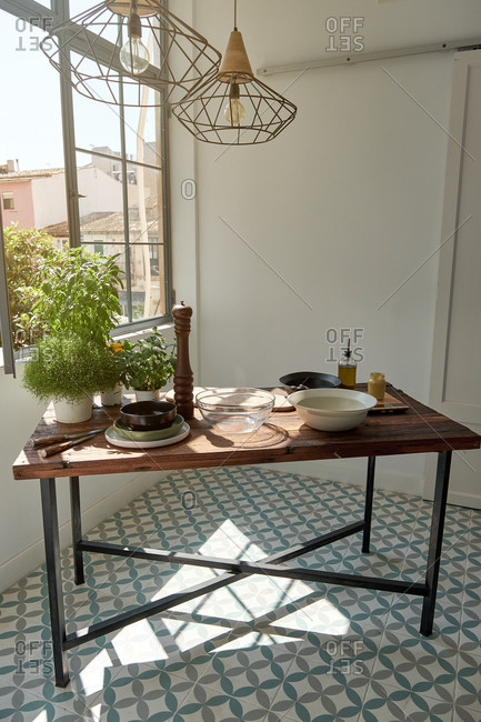 Wooden table served with various kitchenware and placed in room near window on sunny day