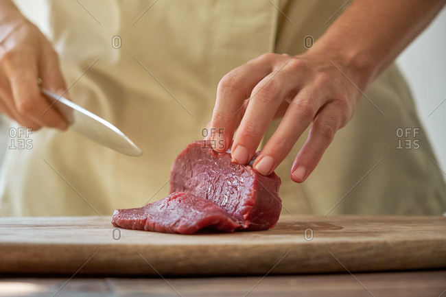 Unrecognizable crop housewife cutting fresh beef on wooden chopping board while preparing delicious Steak tartare for dinner at home