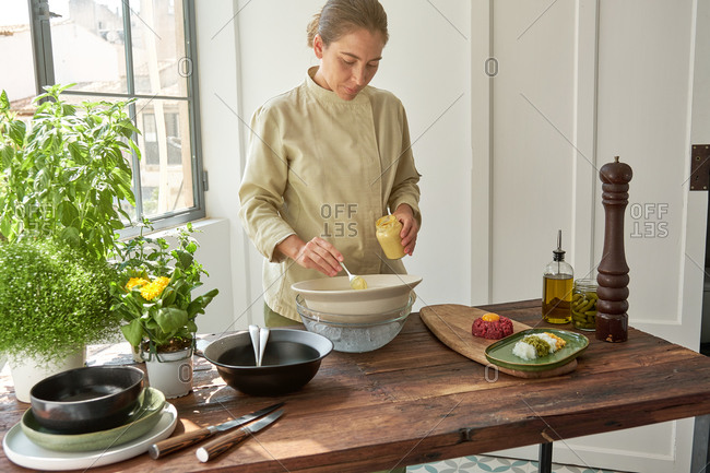 Busy female cook standing at table and adding fresh sauce form glass bottle in bowl while preparing Steak tartare at home