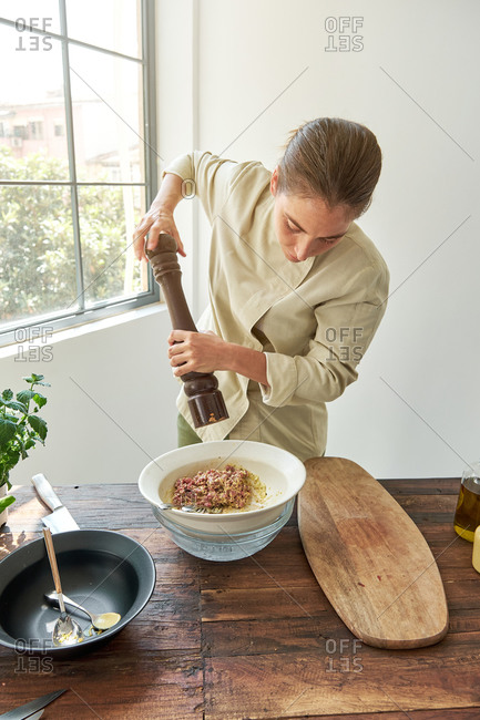 Serious female chef in uniform adding seasonings with pepper mill in bowl with raw beef and mustard while cooking appetizing Steak tartare at home