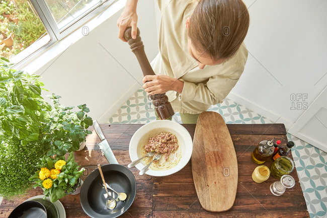 Anonymous woman chef in uniform adding seasonings with pepper mill in bowl with raw beef and mustard while cooking appetizing Steak tartare at home