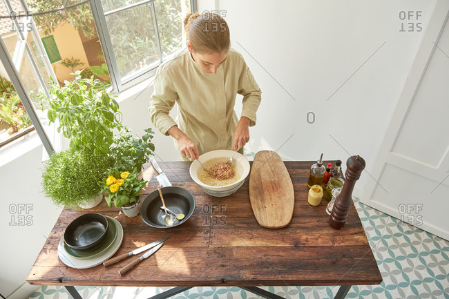 Top view of woman chef in uniform adding seasonings with pepper mill in bowl with raw beef and mustard while cooking appetizing Steak tartare at home