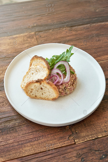 High angle of delicious Steak tartare garnished with onion and fresh rucola served on plate with pieces of bread in cafe