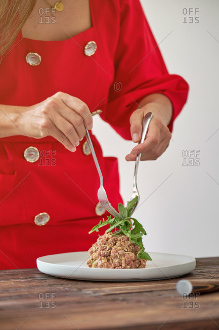 Unrecognizable chef garnishing Steak tartare with fresh green rucola while cooking tasty lunch