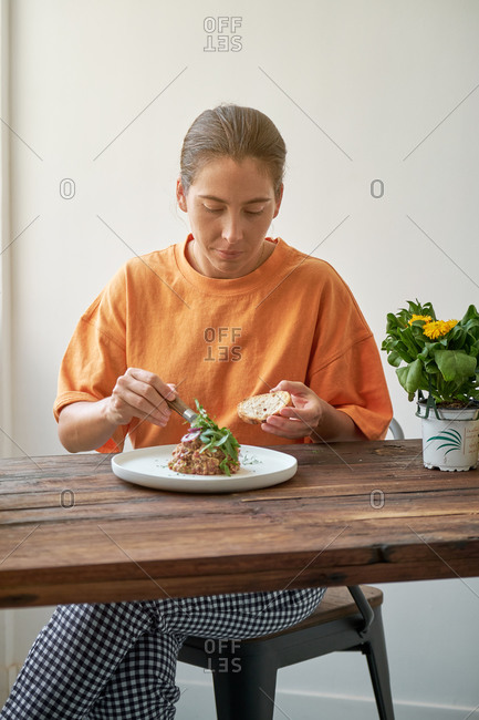 Pensive female sitting at table eating Steak tartare with bread