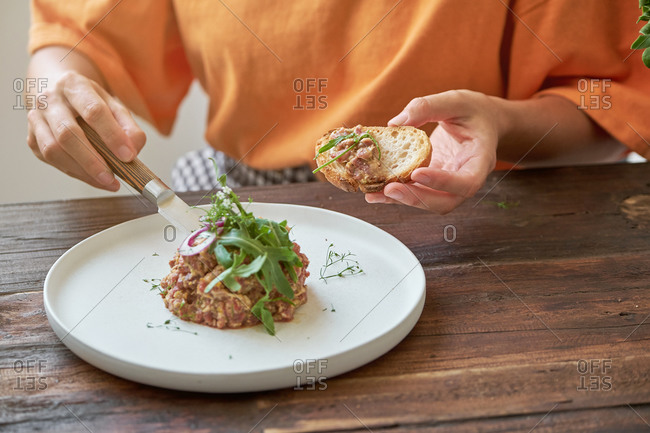Crop view of anonymous woman sitting at table eating Steak tartare with bread