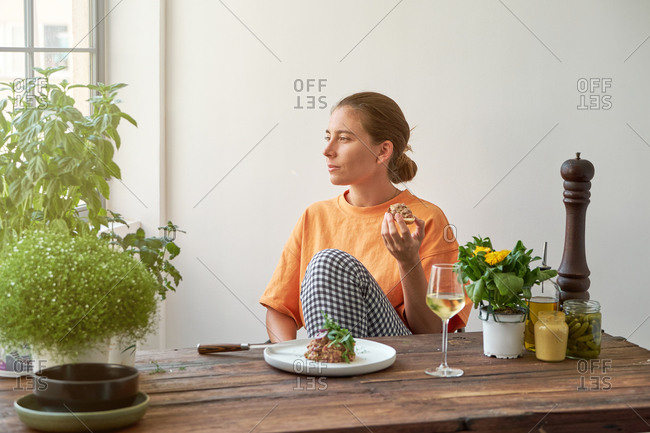 Pensive female sitting at table with Steak tartare on plate and drinking white wine while relaxing at weekend at home and looking at camera
