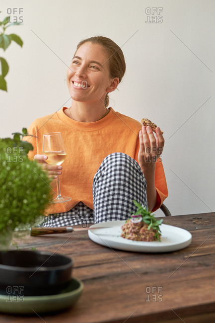 Cheerful woman sitting at table with Steak tartare on plate and drinking white wine while relaxing at home and looking away
