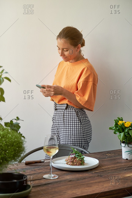 Pensive female browsing cellphone at home while standing near table served with Steak tartare on plate and glass of white wine