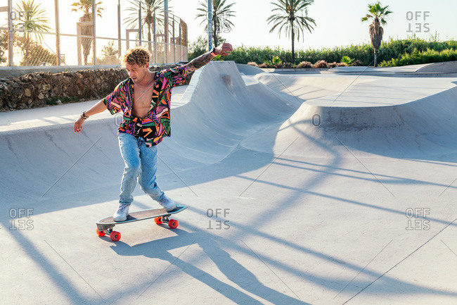 Full body of funky young male skateboarder in trendy colorful shirt and jeans performing trick on concrete ramp while practicing skills in skatepark