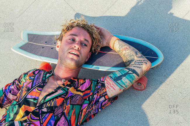 Funky young male skateboarder in trendy colorful shirt resting lying on skate in skatepark