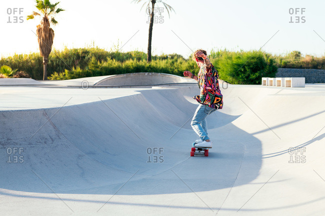 Back view of anonymous funky young male skateboarder in trendy colorful shirt and jeans performing trick on concrete ramp while practicing skills in skatepark
