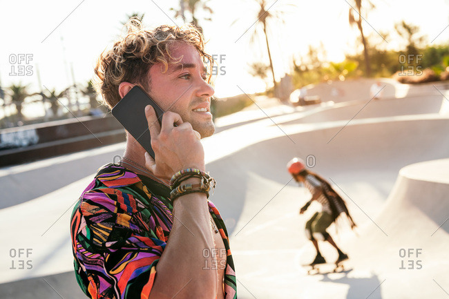Side view of positive millennial curly haired guy in stylish outfit talking on mobile phone while standing near concrete ramp in outdoor skatepark in summer day