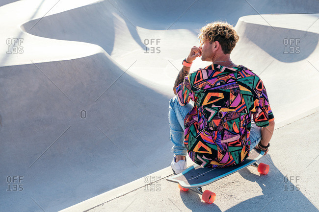High angle back view of trendy tattooed millennial guy with curly hair wearing stylish colorful shirt and jeans sitting on skateboard near ramp in skatepark