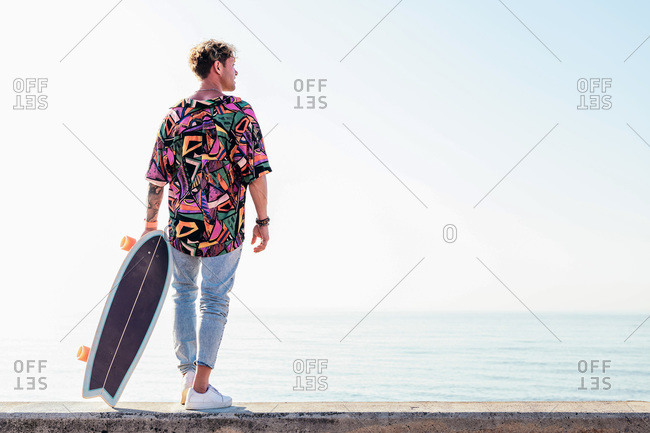 Back view of young hipster male skater in trendy summer outfit carrying skateboard while standing on embankment against sea and cloudless sky in summer day