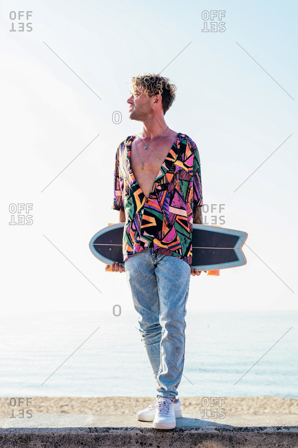 Young hipster male skater in trendy summer outfit carrying skateboard while standing on embankment against sea and cloudless sky in summer day
