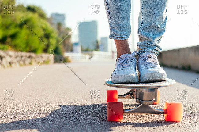 Unrecognizable stylish skater in jeans and sneakers standing on skateboard on street on sunny day in summer