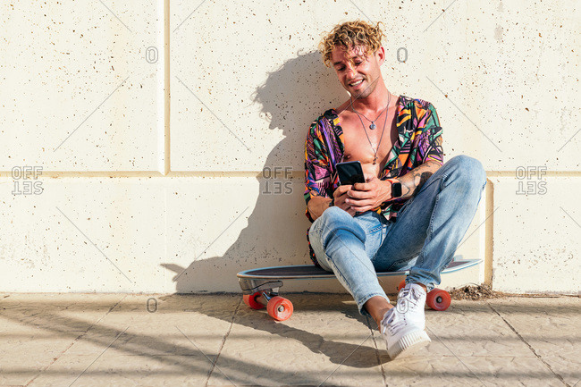Male cheerful hipster sitting on skateboard on lawn in park and chatting on social media via mobile phone on sunny day