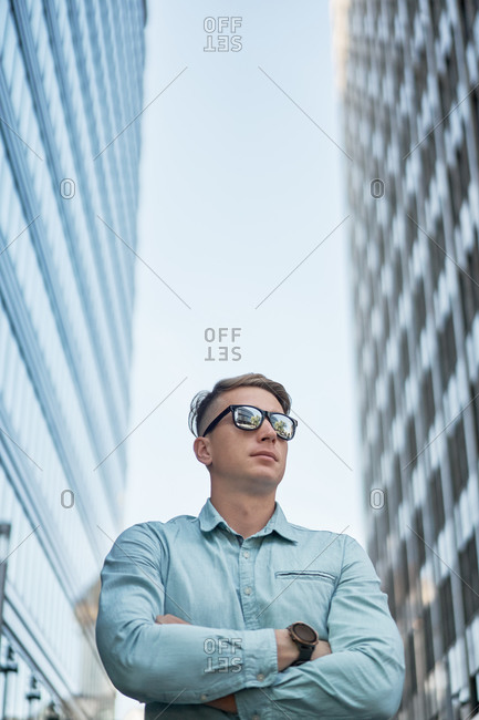 Low angle of serious businessman with sunglasses standing in downtown looking away while waiting for meeting in city