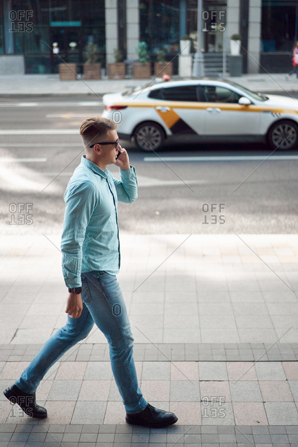 Side view of handsome male in stylish outfit walking along street in city and speaking on smartphone while looking away