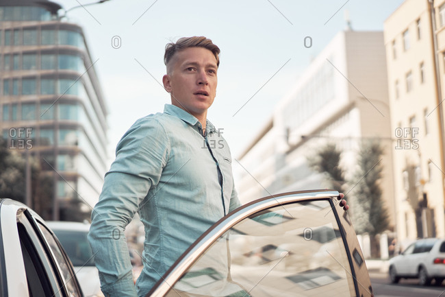 Handsome male driver looking away getting out modern automobile while standing on parking in city