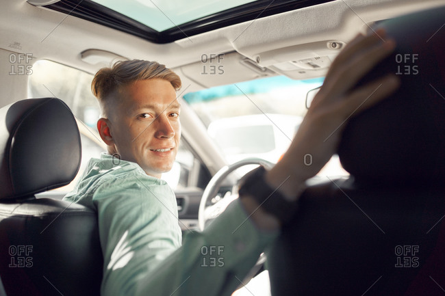 Side view of handsome smiling male driver sitting in parked luxury car and looking at camera