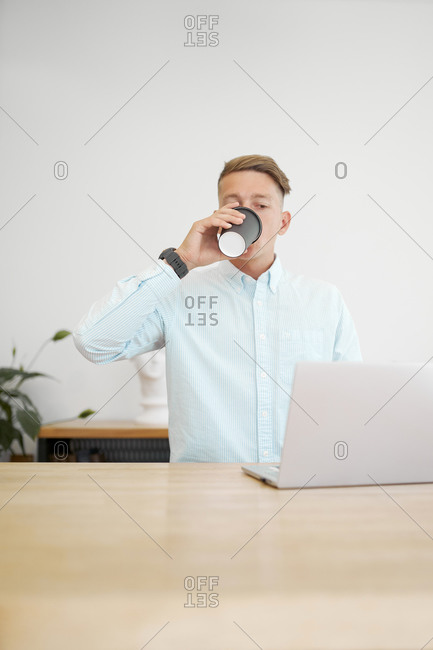 Busy male freelancer sitting at wooden table drinking from a takeaway coffee and working on remote project while browsing netbook