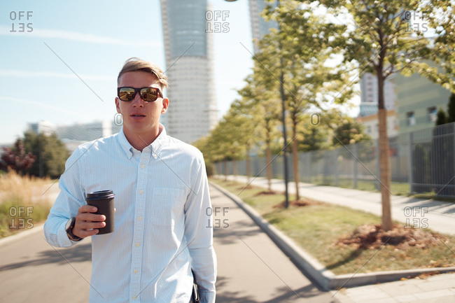 Confident male entrepreneur in stylish sunglasses walking along street with coffee to go during break in city