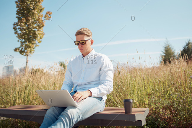 Serious self employed male in stylish sunglasses sitting on bench in park and using netbook while working on startup project